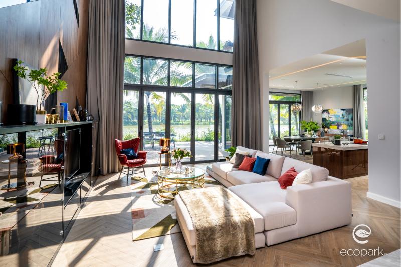 Phòng khách tràn ngập ánh sáng tự nhiên kết hợp với bộ sofa trắng khiến tổng thể thêm bừng sáng